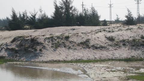 Sau khi chảy qua các cánh đồng và khu dân cư khiến cây cối bị ngập úng, trâu bò bị chết (ảnh trái) thì dòng nước bẩn này lại đổ thẳng ra bãi tắm Thạch Hải. Theo nhiều ngư dân ở đây cho biết thì đã có hiện tượng cá biển chết dạt vào bờ. Ảnh: Hà Vy