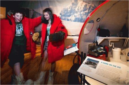 Du khách thử những chiếc áo khoác vùng cực được trưng bày lại cuộc triển lãm. Ảnh: Wyatt/The New York Times.