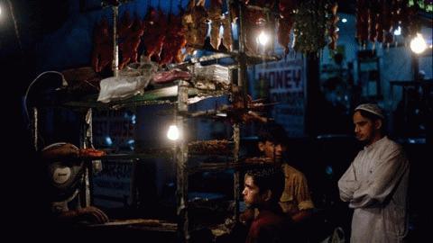 Khi màn đêm buông xuống, các tín đồ Hồi giao những đợi mua thức ăn tại một quầy hàng ở New Delhi ngày 11/8. (Ảnh: FP)