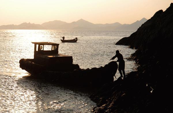 Ông Dai giúp đỡ các tàu thuyền qua đảo (ảnh: xinhua)