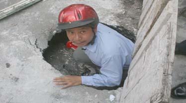 Ông Nguyễn Trọng Hanh, giám đốc Xí nghiệp thoát nước bắc Tàu Hủ xuống ngay hố tử thần. Ảnh: Trần Chánh Nghĩa