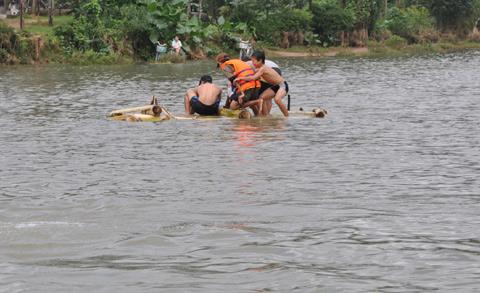 Bất chấp nước lũ đe dọa, nhiều trẻ em ở vùng ngập lũ chèo bè chuối đùa dỡn